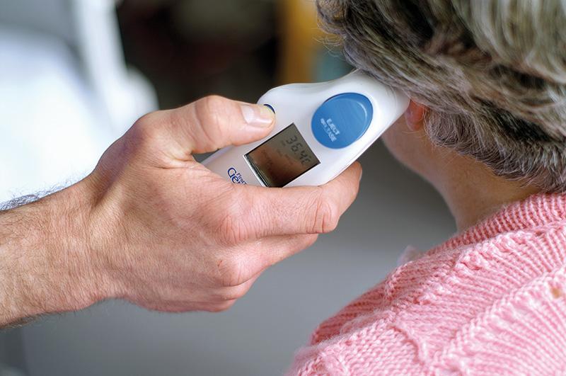 Pflegedienst misst Temperatur im Ohr bei Patientin
