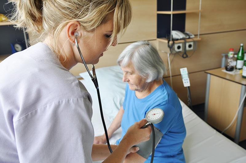 Schwester misst Blutdruck bei Patientin