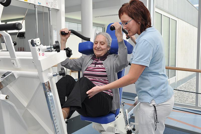 Patientin im Trainingsraum an der Beinpresse mit Therapeutin